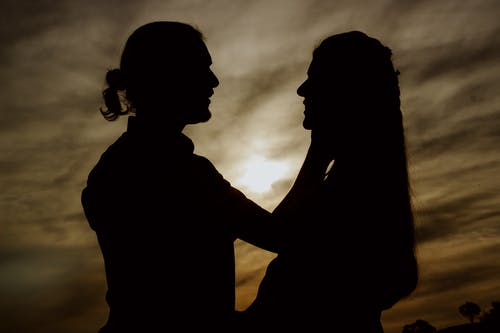 Silhouette of Couple Kissing Under Cloudy Sky