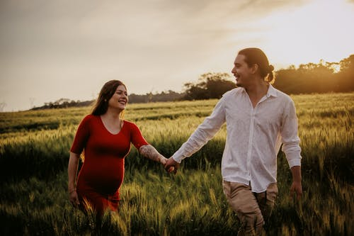 Man and Woman Standing on Green Grass Field