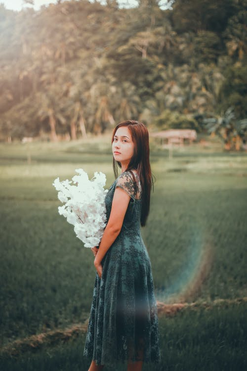 Dreamy ethnic woman in dress with floral branches