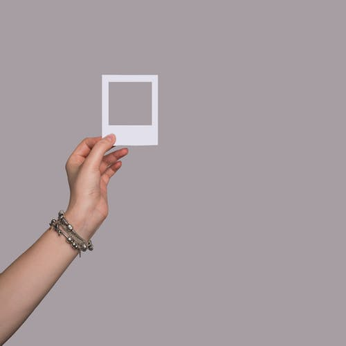 Person Holding White Square Frame