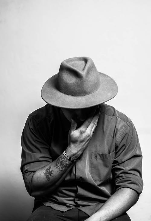 Black and white of anonymous young tattooed male in trendy outfit and hat touching face and looking down while sitting in studio