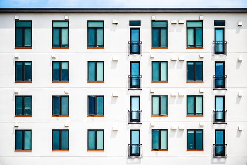 Facade of new white apartment building of simple minimalist style on clear day