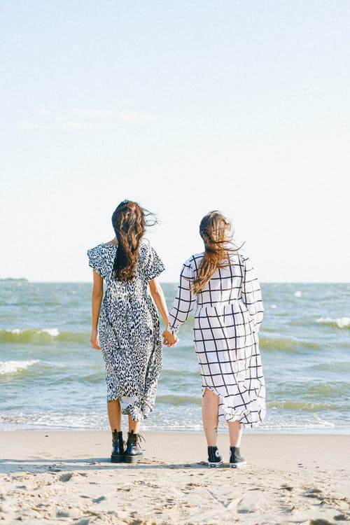 Back view of close women in dresses holding hands while standing on sandy beach near sea