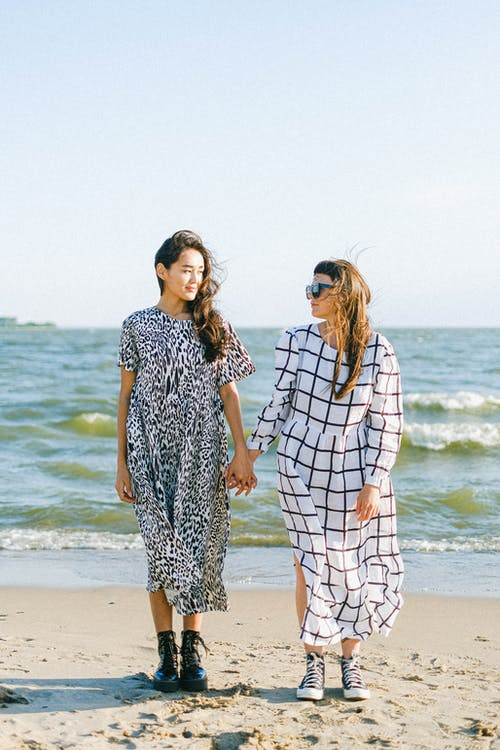 Women standing close on beach in sunny weather