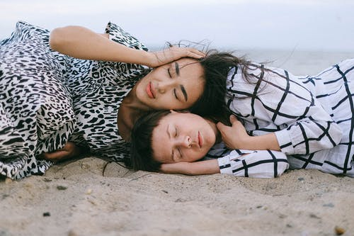 Women Lying on Beach Sand