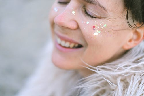 Side view of female with glitter laughing and enjoying moment with closed eyes