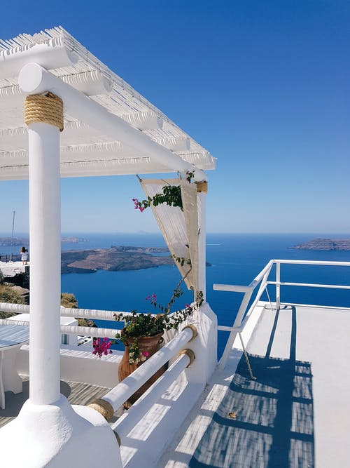 Comfortable white balcony rounded with peaceful turquoise scenery of wide ocean and clear sky on resort