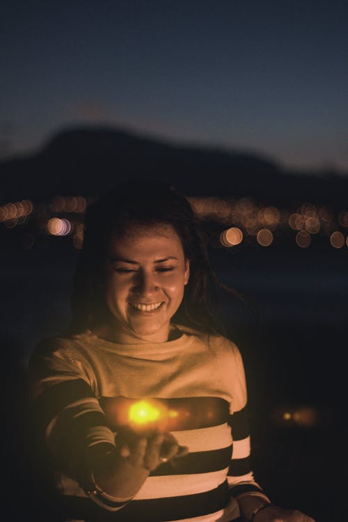Woman in Yellow Crew Neck Shirt Smiling during Night Time