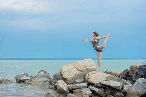 Flexible woman performing yoga on coast of ocean