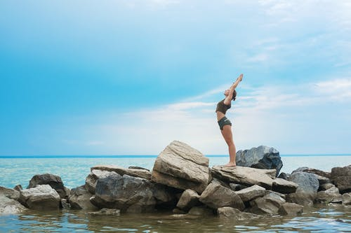 Full body side of young concentrated female in crop top and shorts standing with outstretched arms on big stones on rocky shore of ocean