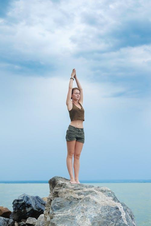 海の海岸で瞑想する集中女性