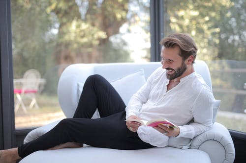 Man in White Dress Shirt and Black Pants Sitting on White Couch