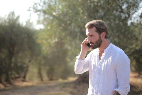 Man in White Dress Shirt Holding Black Smartphone