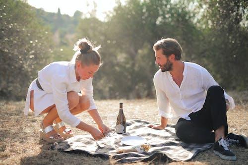 Man in White Dress Shirt Sitting Beside Woman in White Dress Shirt