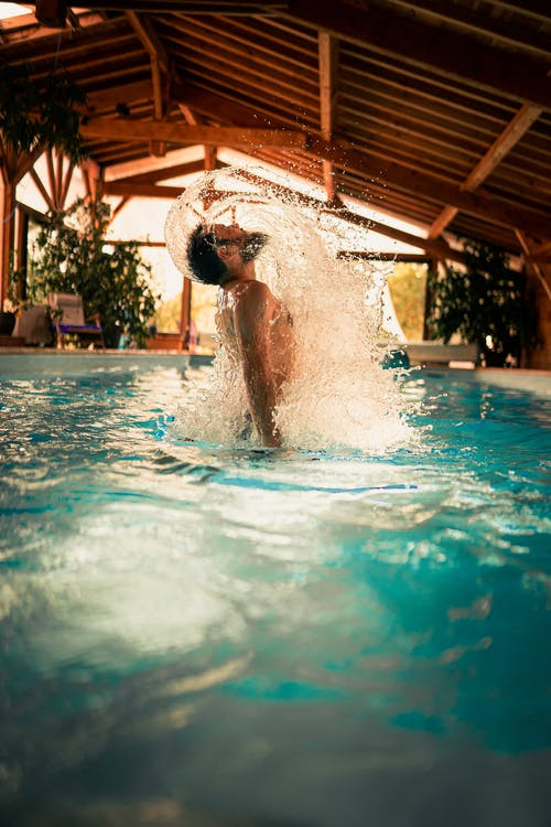 Side view of young male surfacing from water in swimming pool while spending weekend in house
