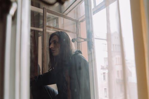 Woman in Black Long Sleeve Shirt Standing Beside Glass Window