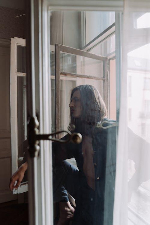 Woman in Blue Shirt Standing Beside Glass Window