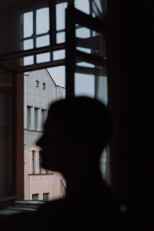 Person in White Shirt Standing Near Window