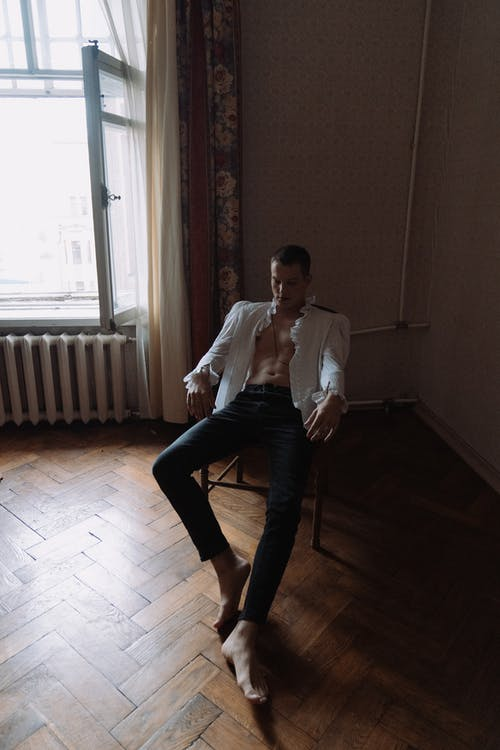 Man in White Dress Shirt and Black Pants Sitting on Chair