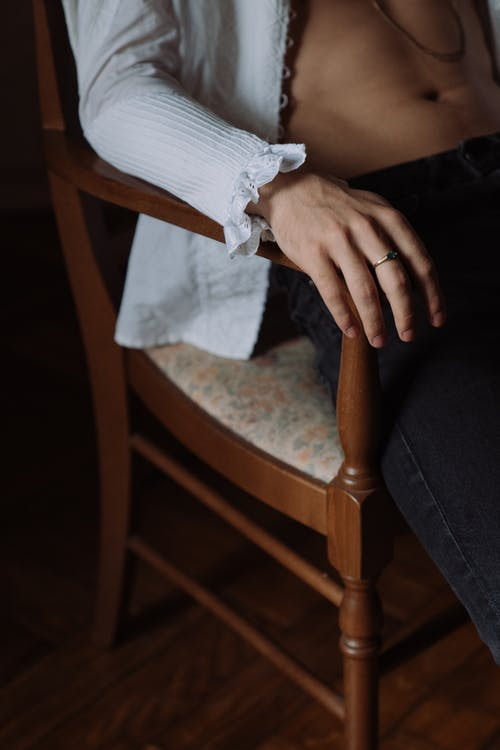 Person in Blue Denim Jeans Sitting on Brown Wooden Chair