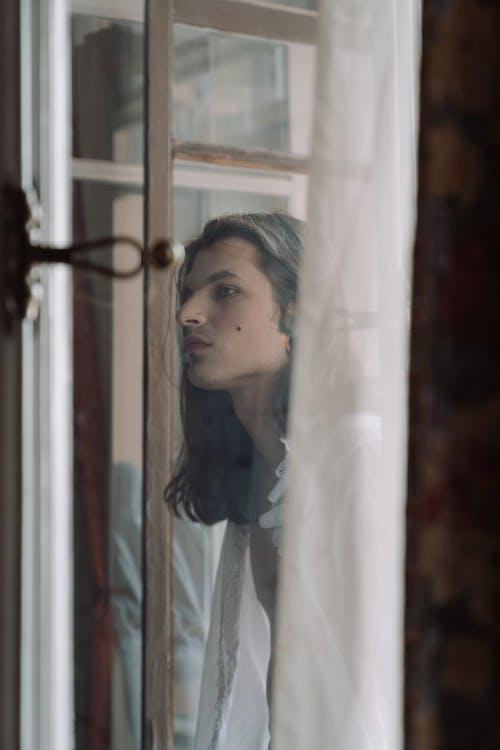Woman in White Dress Shirt Standing Near Window