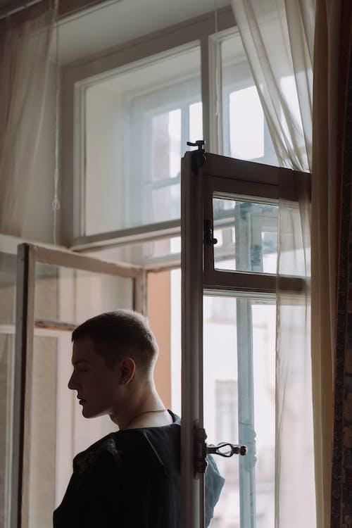Man in White Shirt Standing Near Window
