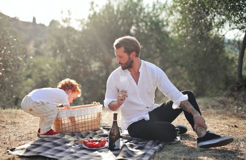 Man in White Dress Shirt Holding Bottle and Woman in White Long Sleeve Shirt