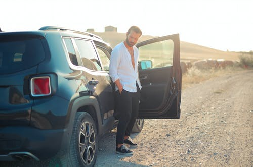 Man in White Dress Shirt and Black Pants Standing Beside Black Suv