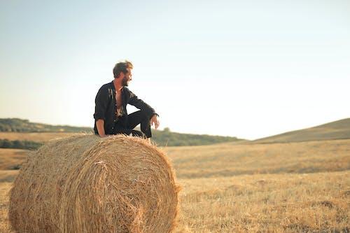 Man in Black Jacket Standing on Brown Grass Field