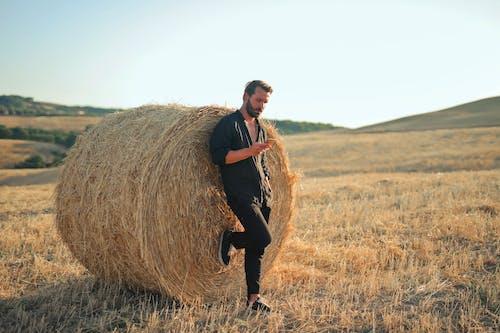 Man in Black Jacket and Black Pants Sitting on Brown Hay Roll