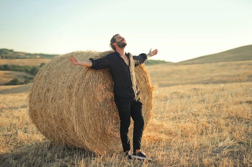 Man in Black Jacket and Black Pants Standing on Brown Grass Field
