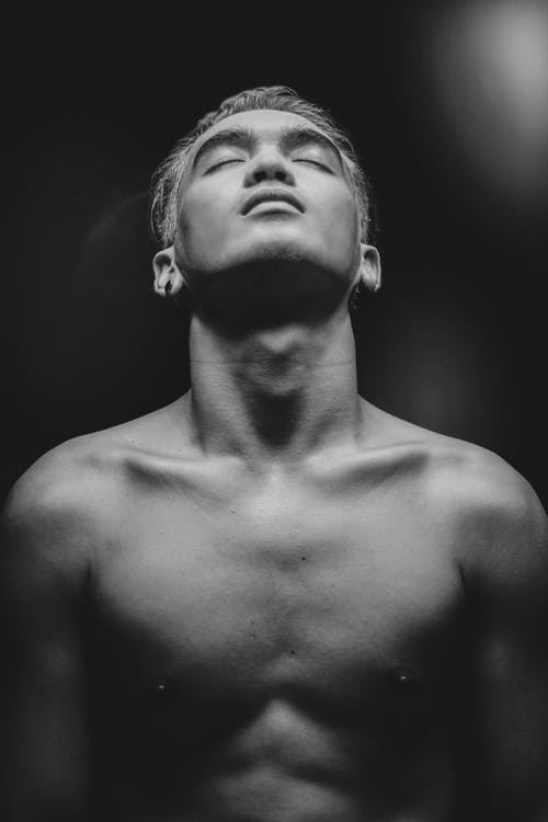 Young ethnic man with naked torso and closed eyes