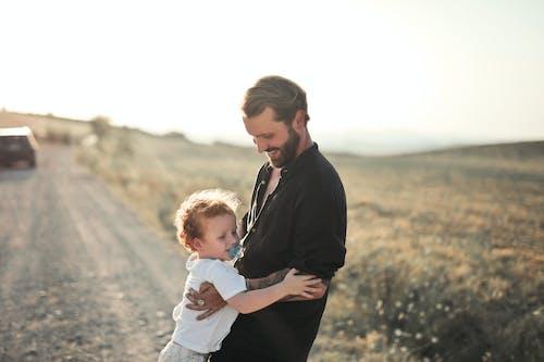 Man in Black Jacket Carrying Baby in White Onesie