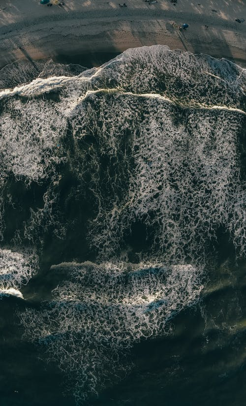 Drone top view of calm foamy sea waves running on sandy beach in early evening light