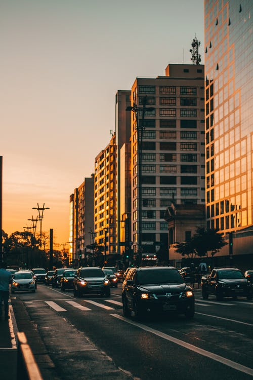 Various cars driving on asphalt road against picturesque sunset sky reflecting in glass mirrored facades of modern multistory buildings