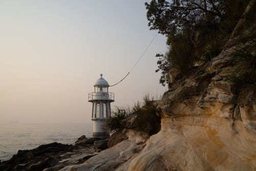 White Lighthouse on Brown Rocky Hill Near Body of Water
