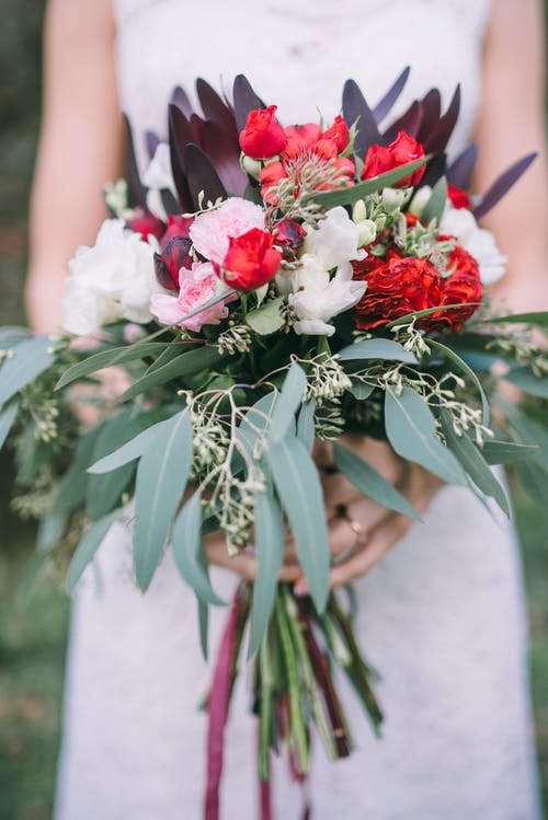 Woman in White Wedding Dress Holding Red and White Flower Bouquet