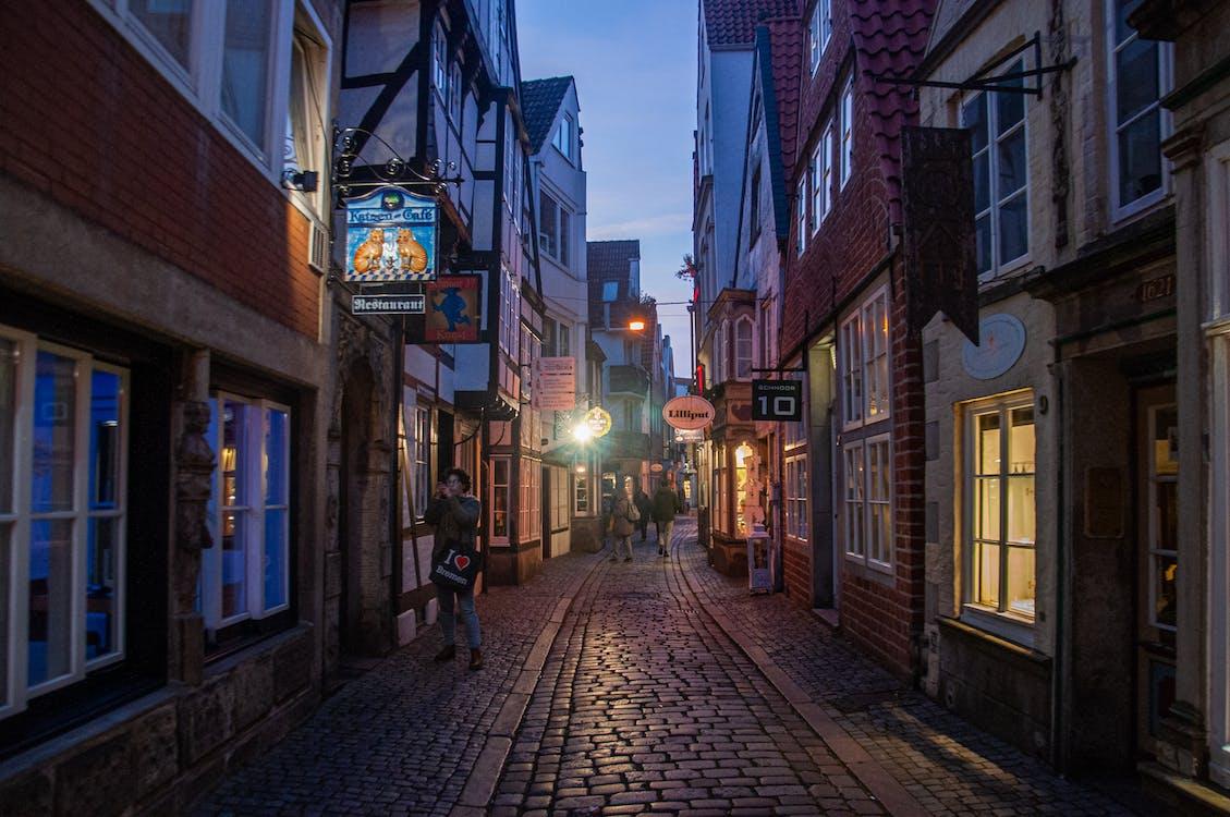 People Walking on Sidewalk Between Buildings during Night Time