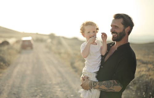 Man in Black Suit Jacket Holding Baby in White Long Sleeve Shirt