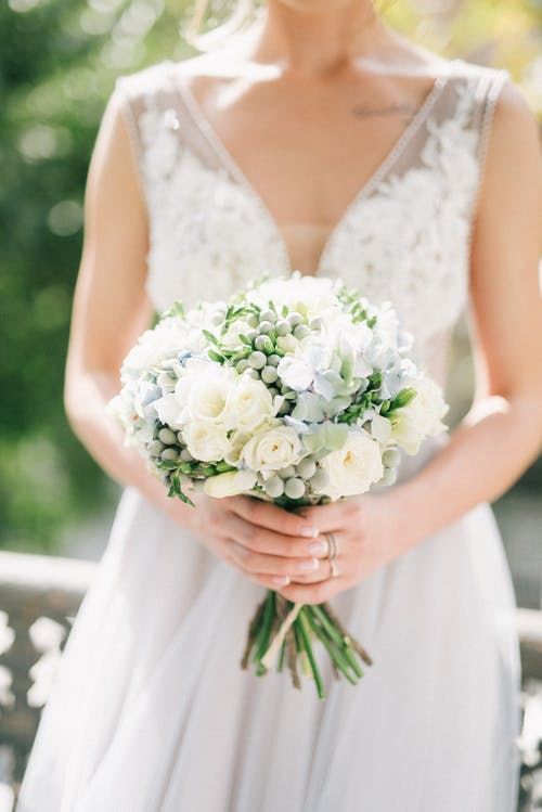 Woman in White Floral Dress Holding Bouquet of White Roses