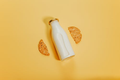 Bottle of milk with cookies on surface