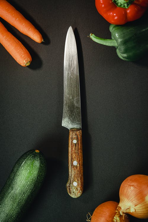 Long knife with wooden handle surrounded by different colorful vegetables and placed on black background in kitchen with ingredients for cooking