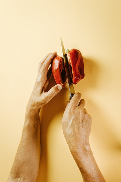 Crop person cutting red bell pepper