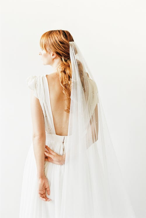 Tender bride in veil and backless dress