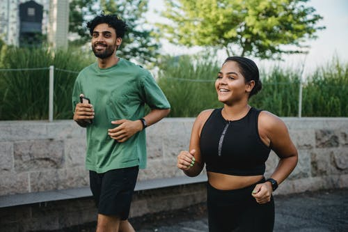 Man and Woman Smiling While Jogging Together