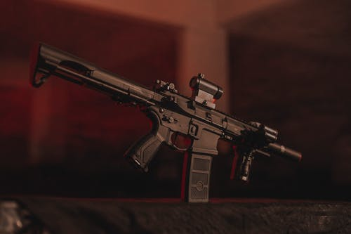 Black and Brown Rifle on Black Textile