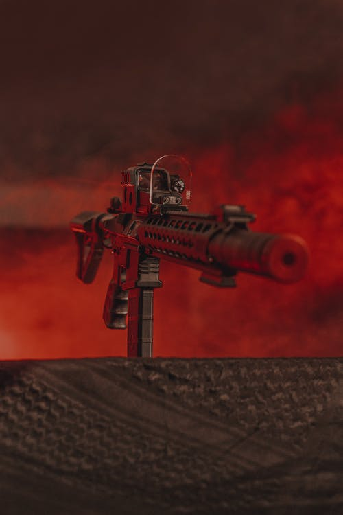 Black and Red Rifle on Brown Wooden Table