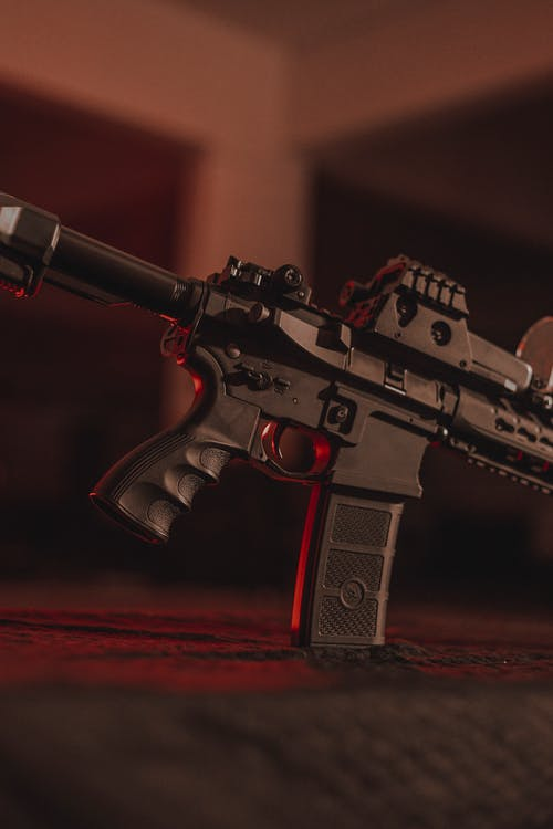 Black and Gray Rifle on Brown Wooden Table