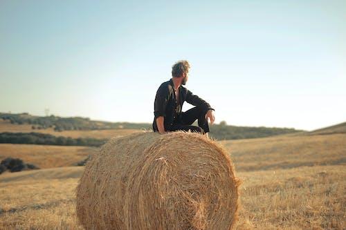 Man in Black Jacket Standing Beside Brown Hay Roll