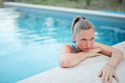 Girl in Blue and White Bikini Lying on White Concrete Floor Near Swimming Pool